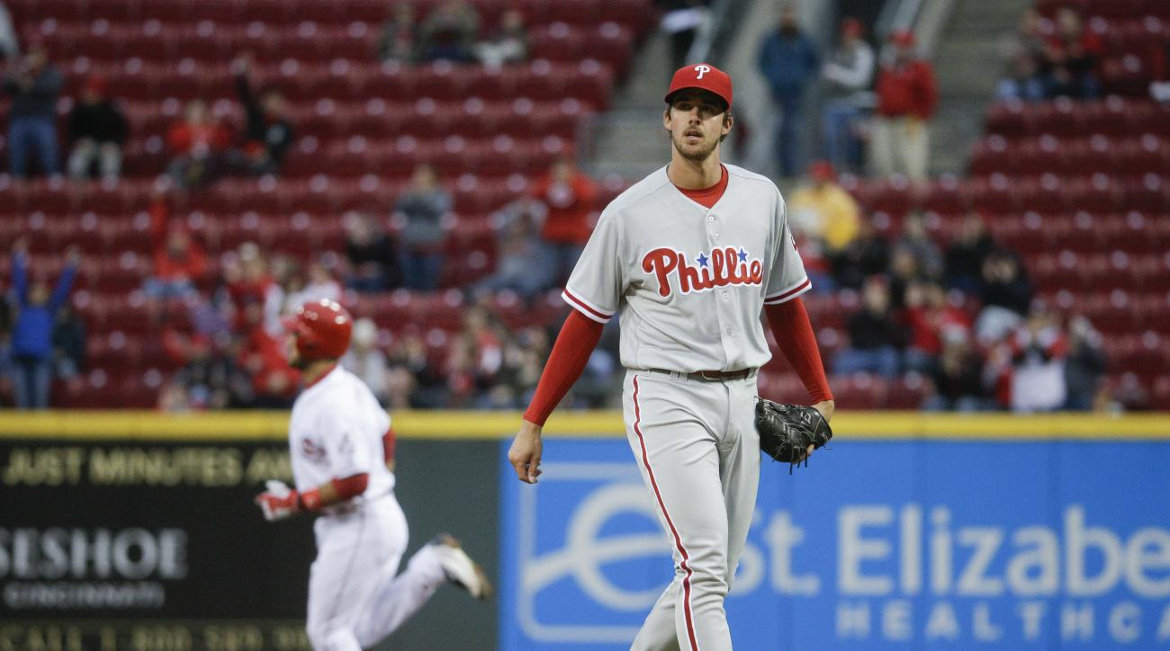Philadelphia Phillies starting pitcher Aaron Nola, right, reacts after Cincinnati Reds' Eugenio Suarez, left, hit a solo home run during the first inning of a baseball game, Wednesday, April 6, 2016, in Cincinnati. (AP Photo/John Minchillo)