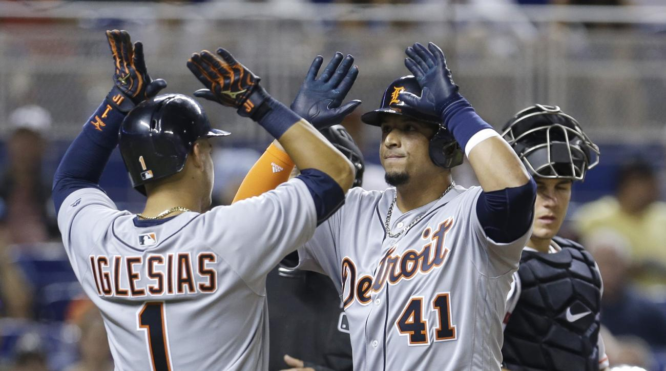 Detroit Tigers' Victor Martinez (41) is congratulated by Jose Iglesias (1) after Martinez hit a two-run home run against the Miami Marlins in the eighth inning of an interleague baseball game, Wednesday, April 6, 2016, in Miami. The Tigers won 7-3. (AP Ph