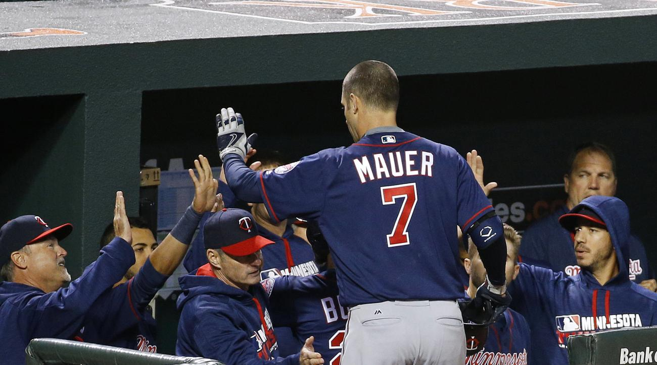 Minnesota Twins' Joe Mauer (7) high-fives teammates after hitting a sacrifice fly ball in the third inning of a baseball game against the Baltimore Orioles in Baltimore, Wednesday, April 6, 2016. Byron Buxton scored on the play. (AP Photo/Patrick Semansky