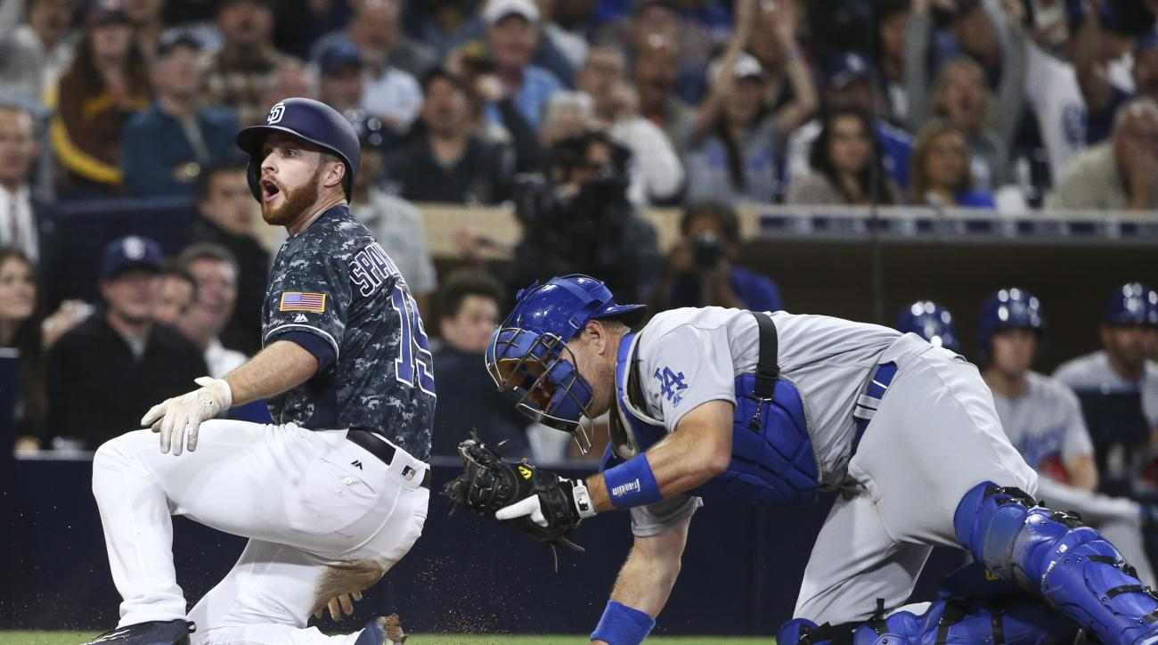 San Diego Padres' Cory Spangenberg reacts to the umpire's out call as Los Angeles Dodgers catcher A.J. Ellis holds the ball during the sixth inning of a baseball game Wednesday, April 6, 2016, in San Diego. (AP Photo/Lenny Ignelzi)
