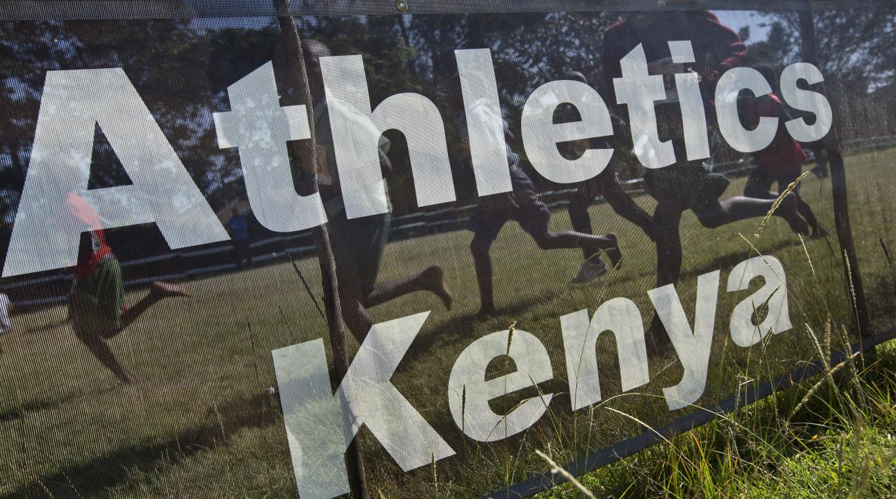 FILE - In this Sunday, Jan. 31, 2016 file photo, junior athletes run past a sign for Athletics Kenya at the Discovery cross country races, an annual race held to identify up-and-coming new young talent, in Eldoret, Kenya. The World Anti-Doping Agency (WAD