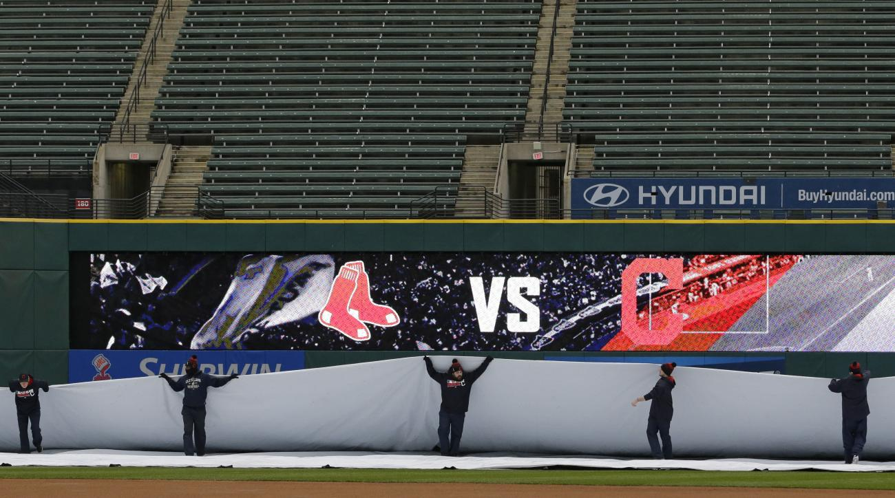 Members of the grounds crew pull the tarp on the field after a baseball game between the Boston Red Sox and the Cleveland Indians was postponed due to inclement weather, Thursday, April 7, 2016, in Cleveland. (AP Photo/Tony Dejak)
