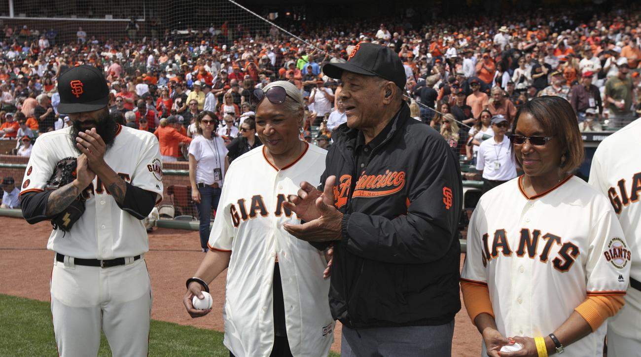 Hall of Famer Willie Mays stands with Pamela Irvin Fields, second from left, and Patricia Irvin Gordon, right, the daughters of Hall of Famer Monte Irvin, before the start of an opening day baseball game between the San Francisco Giants and Los Angeles Do