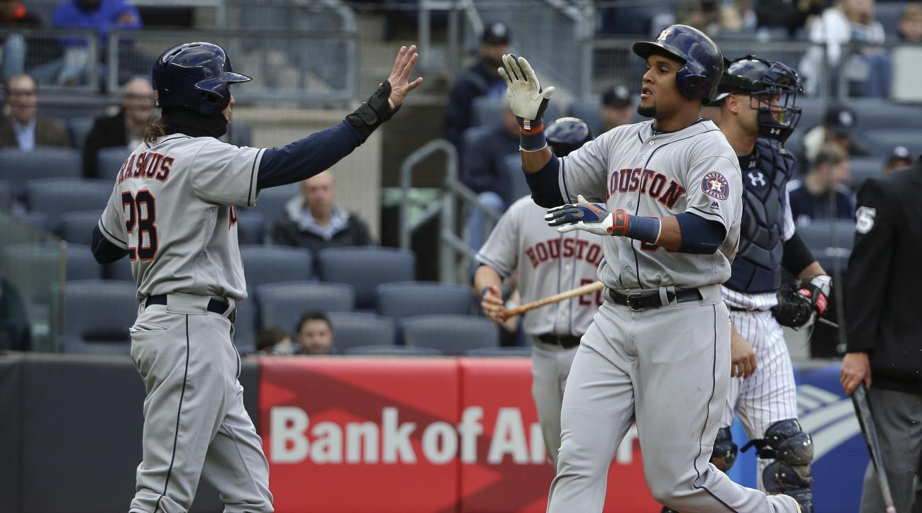 Houston Astros ' Carlos Gomez, right, is greeted by teammate Colby Rasmus (28) after scoring against the New York Yankees during the fourth inning of a baseball game, Thursday, April 7, 2016, in New York. (AP Photo/Julie Jacobson)
