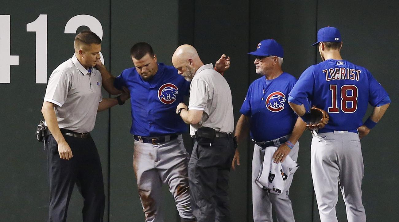 An injured Chicago Cubs' Kyle Schwarber, second from left, is attended to by training staff as manager Joe Maddon, second from right, and Ben Zobrist (18) look on during the second inning of a baseball game against the Arizona Diamondbacks Thursday, April