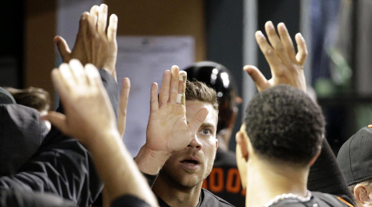 Baltimore Orioles' Chris Davis, center, high-fives teammates after scoring on a single by teammate Matt Wieters in the fourth inning of a baseball game against the Tampa Bay Rays in Baltimore, Friday, April 8, 2016. (AP Photo/Patrick Semansky)