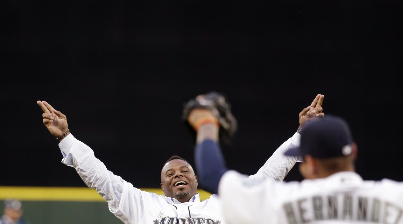 Former Seattle Mariners player Ken Griffey Jr., left, playfully mimics the motion made by Mariners pitcher Felix Hernandez (34) from a no-hitter years earlier, after Griffey threw out the ceremonial first pitch before the Mariner' home-opener baseball gam