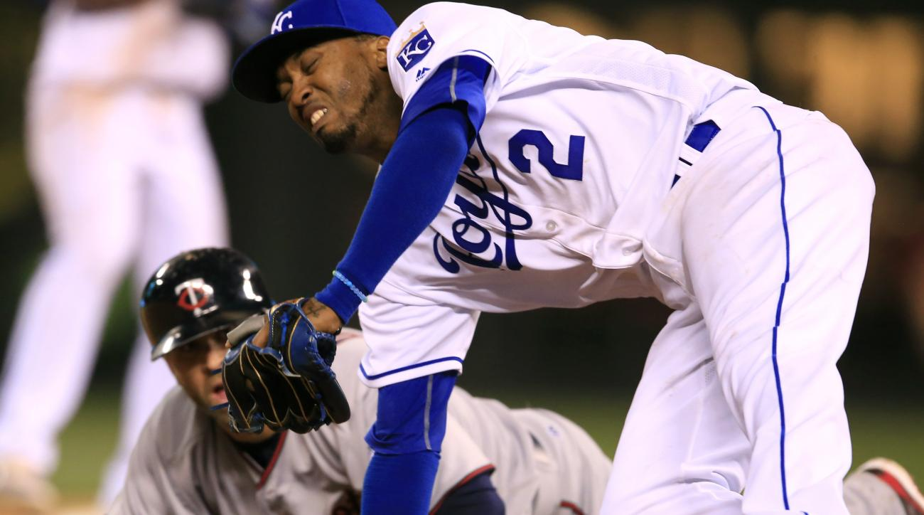 Kansas City Royals shortstop Alcides Escobar (2) falls over Minnesota Twins' Brian Dozier during a rundown between second and third bases in the ninth inning of a baseball game at Kauffman Stadium in Kansas City, Mo., Friday, April 8, 2016. Dozier was out