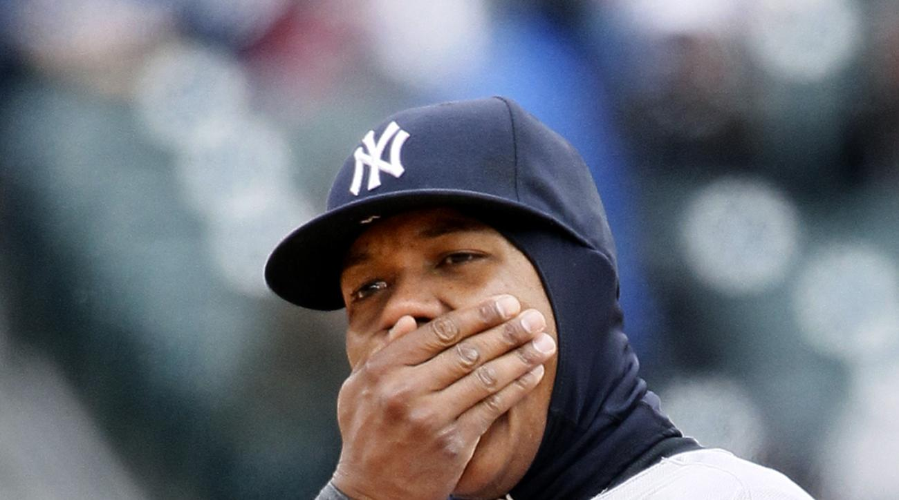 New York Yankees' Starlin Castro tries to keep his hand warm while playing second base against the Detroit Tigers during the fourth inning of a baseball game Saturday, April 9, 2016, in Detroit. (AP Photo/Duane Burleson)
