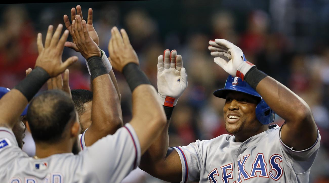 Texas Rangers'  Adrian Beltre, right, is congratulated by teammate Rougned Odor (12) after hitting a solo home run in the fourth inning of a baseball game against the Los Angeles Angels in Anaheim, Calif., Saturday, April 9, 2016. (AP Photo/Christine Cott