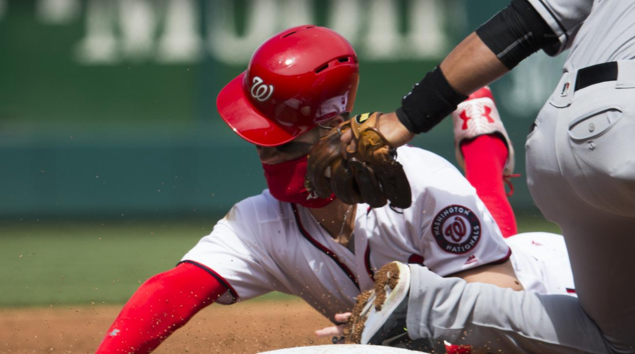 Washington Nationals Bryce Harper is tagged out while trying to steal a base by Miami Marlins third baseman Martin Prado during the first inning of a baseball game at Nationals Park on Sunday, April 10, 2016, in Washington. (AP Photo/Evan Vucci)