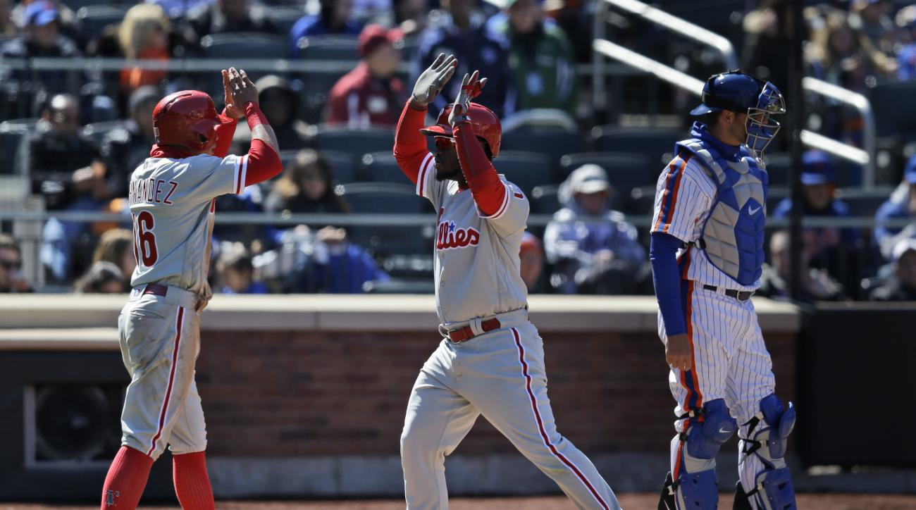 While New York Mets catcher Kevin Plawecki, right, looks toward the field, Philadelphia Phillies' Odubel Herrera, center, celebrates his two-run home run with Cesar Hernandez during the sixth inning of the baseball game at Citi Field, Sunday, April 10, 20
