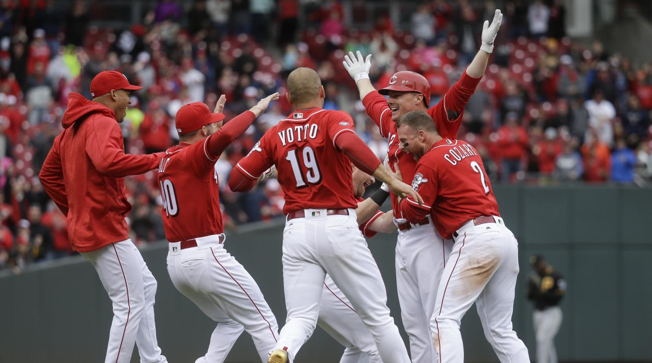 Cincinnati Reds' Jay Bruce, second from right, celebrates with his teammates after hitting a walk-off triple in the ninth inning of a baseball game against the Pittsburgh Pirates, Sunday, April 10, 2016, in Cincinnati. The Reds won 2-1. (AP Photo/John Min