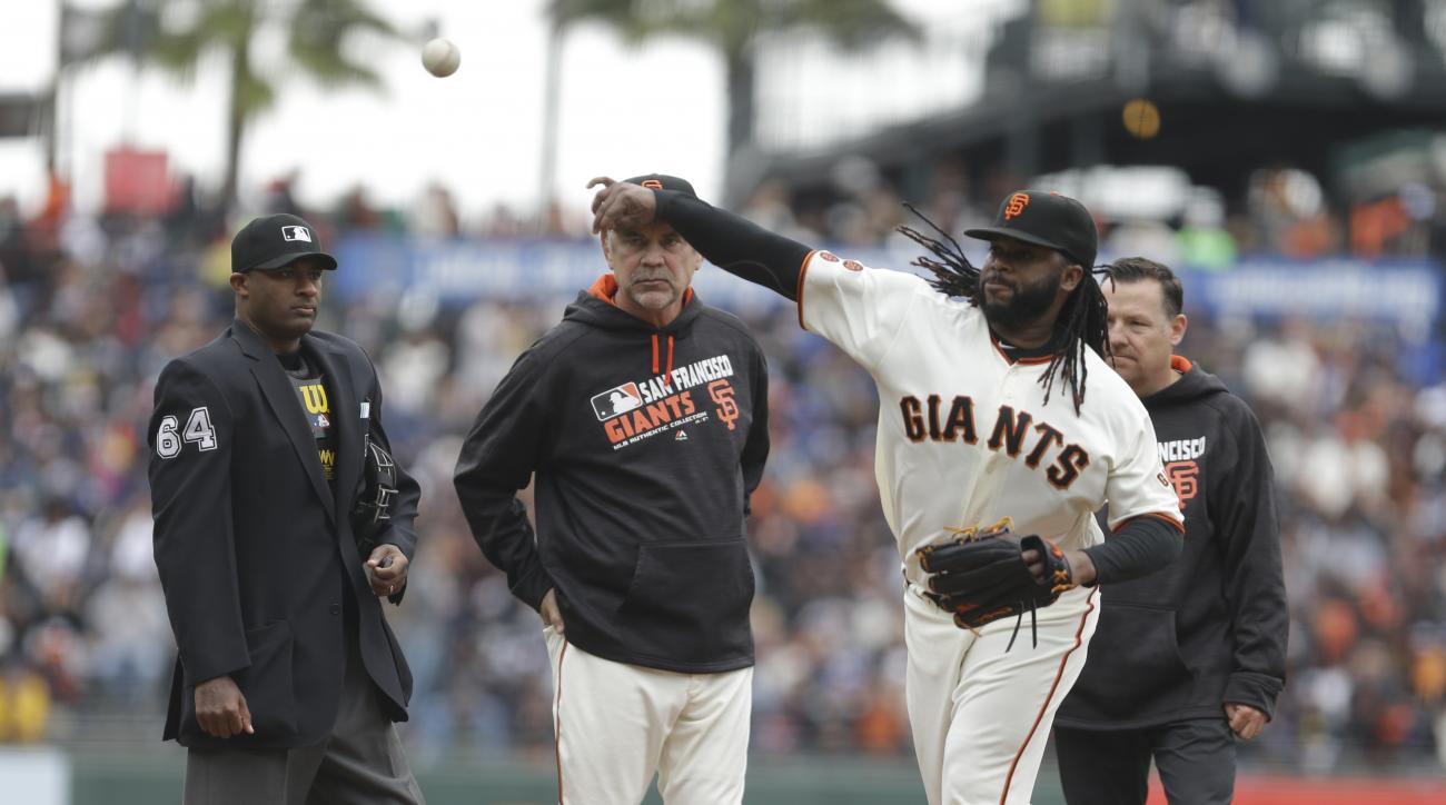 FILE - In this April 10, 2016, file photo, San Francisco Giants pitcher Johnny Cueto is examined by home plate umpire Alan Porter, left, and manager Bruce Bochy in the first inning of a baseball game against the Los Angeles Dodgers in San Francisco. Major
