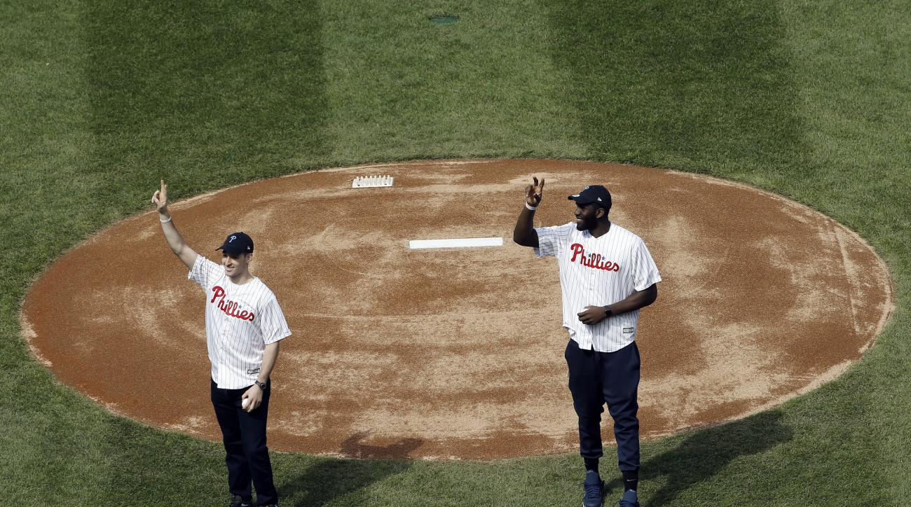 Villanova's Ryan Arcidiacono, left, and Daniel Ochefu, gesture to fans before throwing out ceremonial pitches ahead of the Philadelphia Phillies' home opening day baseball game against the San Diego Padres, Monday, April 11, 2016, in Philadelphia. (AP Pho