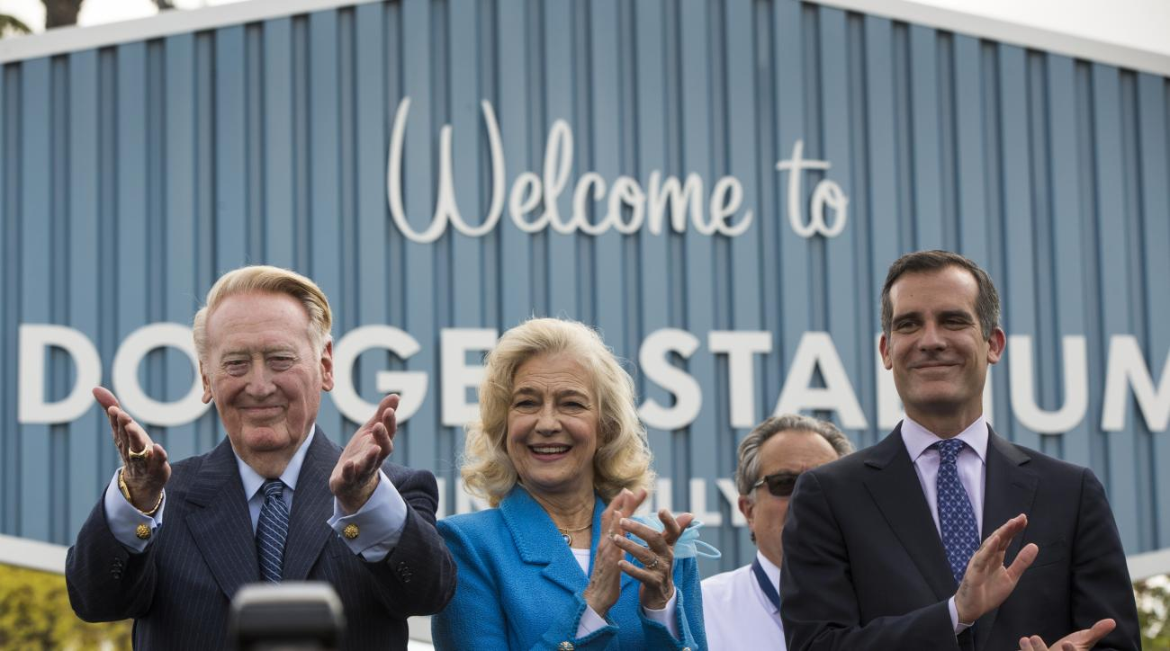 Dodger legend Vin Scully, left, with his wife, Sandra Hunt, thanks Dodgers' fans at a dedication ceremony unveiling a street sign of his namesake at the entrance to Dodger Stadium in Los Angeles on Monday, April 11, 2016. At right is Los Angeles Mayor Eri