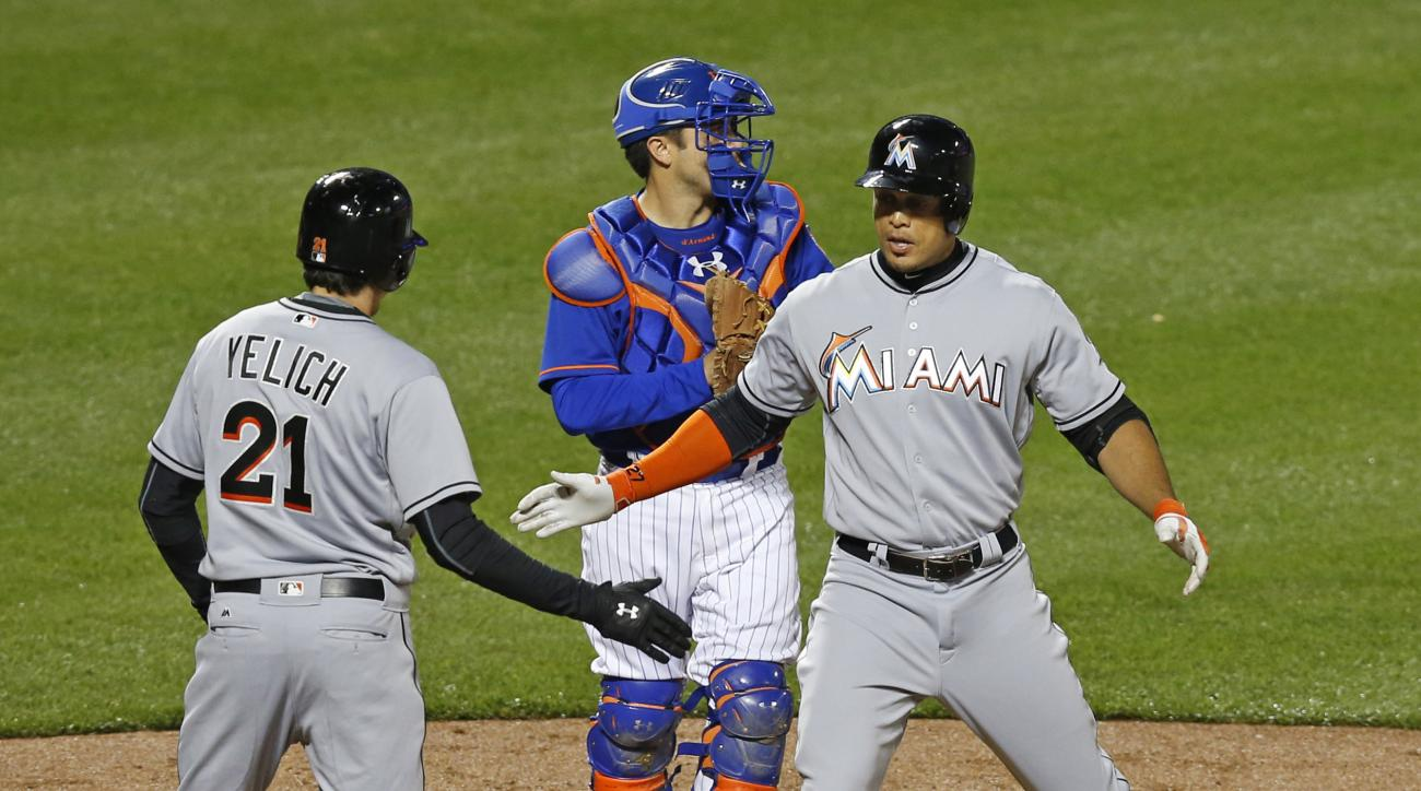 Miami Marlins Giancarlo Stanton greets Christian Yelich (21) after hitting a second-inning, two-run, home run in a baseball game against the New York Mets, Monday, April 11, 2016, in New York. Mets catcher Travis d'Arnaud, center, looks to the outfield. (