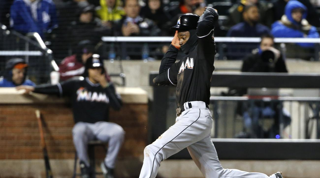 Miami Marlins' Dee Gordon runs home to score on Martin Prado's eighth-inning sacrifice fly in a baseball game against the New York Mets, Tuesday, April 12, 2016, in New York. (AP Photo/Kathy Willens)