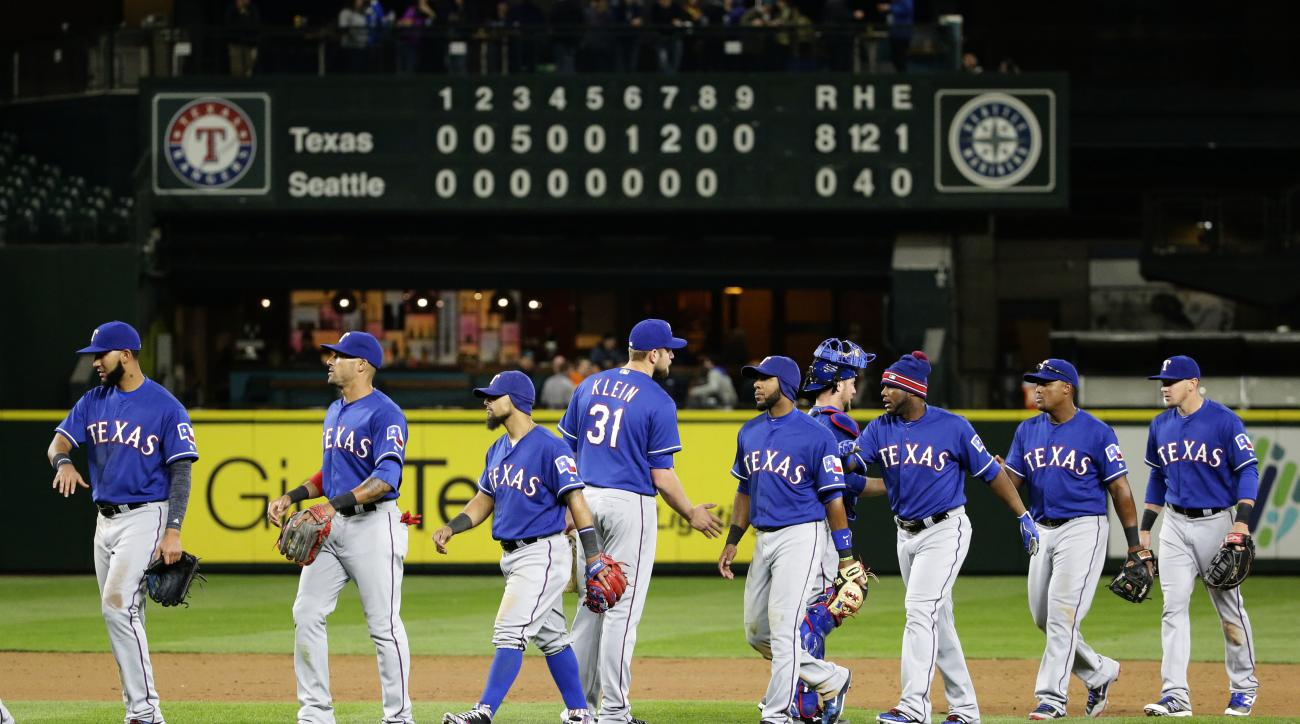 Texas Rangers players greet each other after the Rangers defeated the Seattle Mariners 8-0 in a baseball game, Tuesday, April 12, 2016, in Seattle. (AP Photo/Ted S. Warren)