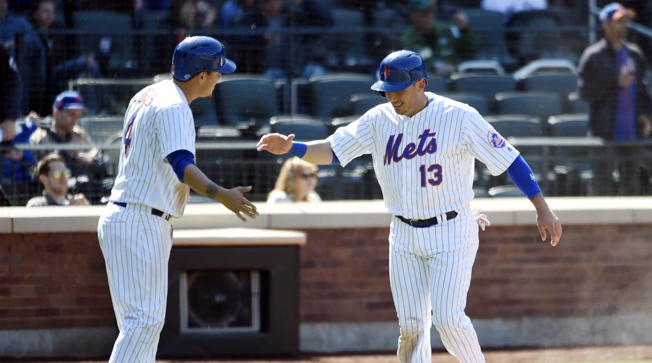 New York Mets Wilmer Flores (4) greets Asdrubal Cabrera (13) at home plate after they both scored on Kevin Plawecki's single in the seventh inning of a baseball game, Wednesday, April 13, 2016, in New York. (AP Photo/Kathy Kmonicek)