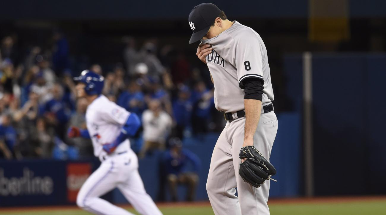 Toronto Blue Jays' Troy Tulowitzki rounds the bases after hitting a run home as New York Yankees starting pitcher Nathan Eovaldi wipes his face during the sixth inning of a baseball game Thursday, April 14, 2016, in Toronto. (Frank Gunn/The Canadian Press