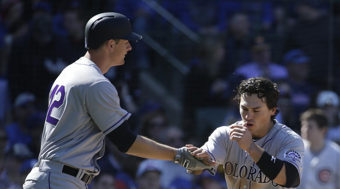 Colorado Rockies' Tony Wolters, right, celebrates with teammate DJ LeMahieu, left, after scoring on a wild throw by Chicago Cubs third baseman Kris Bryant during the seventh inning of a baseball game Friday, April 15, 2016, in Chicago. (AP Photo/Nam Y. Hu