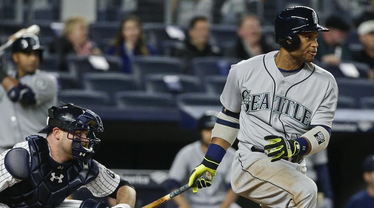 Seattle Mariners' Robinson Cano follows through on an RBI single during the fourth inning of a baseball game as New York Yankees catcher Brian McCann watches, Friday, April 15, 2016, in New York. (AP Photo/Frank Franklin II)
