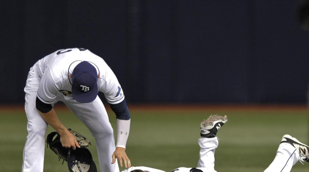 Tampa Bay Rays right fielder Brandon Guyer, left, aids center fielder Kevin Kiermaier, right, after Kiermaier's collision with infielder Logan Forsythe while chasing down a fly ball hit by Chicago White Sox's Avisail Garcia during the fourth inning of a b