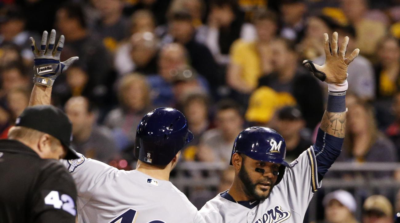 Milwaukee Brewers' Ryan Braun, center, celebrates with teammate Jonathan Villar, right, after hitting a two-run home run off Pittsburgh Pirates starting pitcher Kyle Lobstein during the sixth inning of a baseball game in Pittsburgh, Friday, April 15, 2016