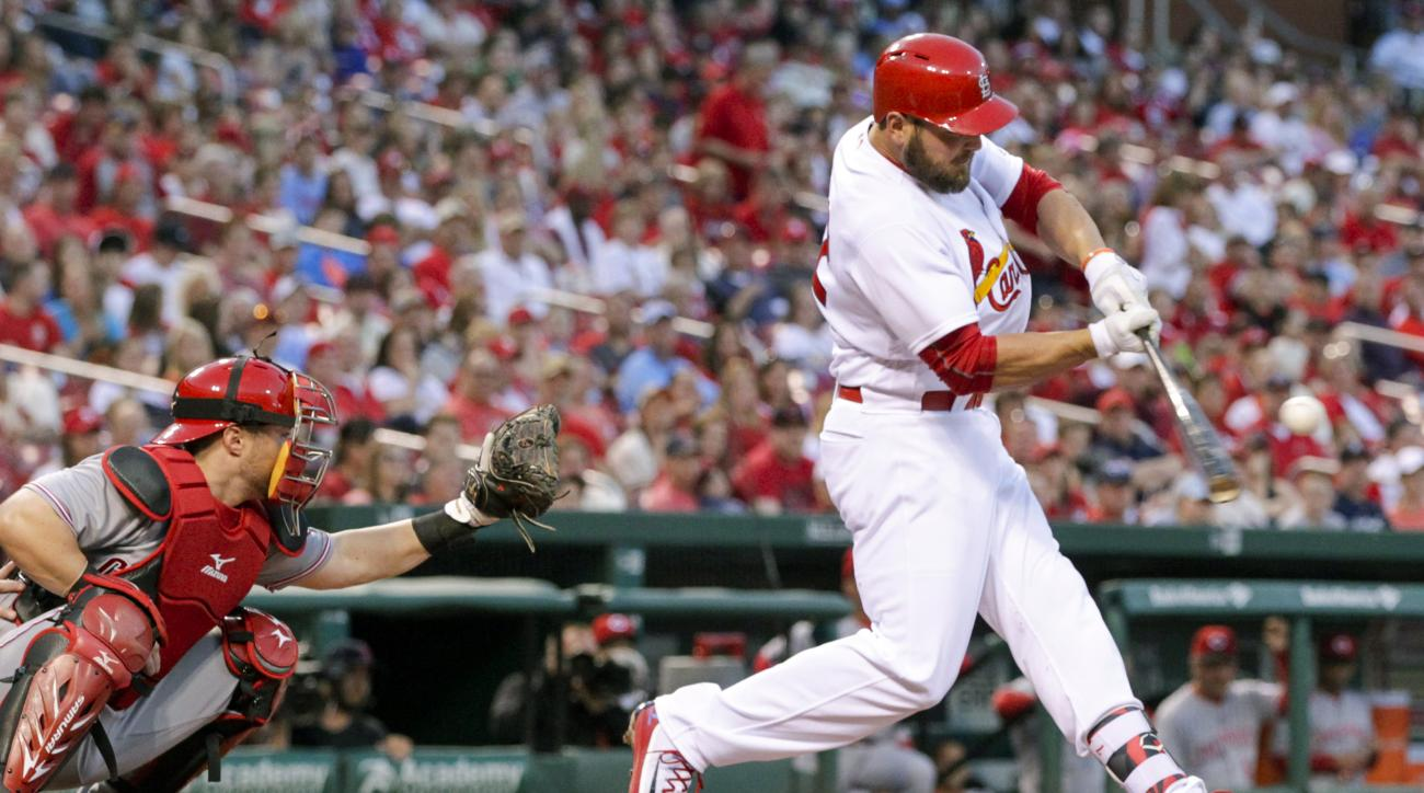 St. Louis Cardinals' Matt Holliday, right, connects for a three-run home run as Cincinnati Reds catcher Tucker Barnhart watches in the first inning of a baseball game, Friday, April 15, 2016, in St. Louis. (AP Photo/Tom Gannam)