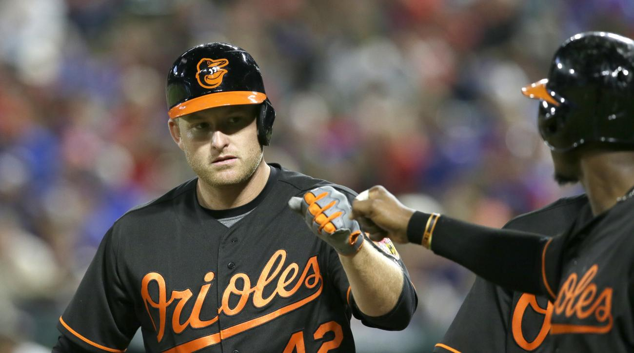 Baltimore Orioles designated hitter Mark Trumbo, left, is congratulated by teammate Adam Jones after hitting a  three-run home run during the seventh inning of a baseball game against the Texas Rangers in Arlington, Texas, Friday, April 15, 2016. (AP Phot