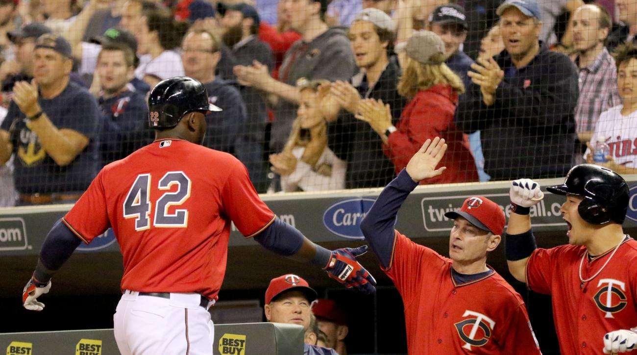 Minnesota Twins' Miguel Sano, left, gets a high-five from manager Paul Molitor and Byung Ho Park after scoring against the Los Angeles Angels in the sixth inning of a baseball game Friday, April 15, 2016, in Minneapolis. (David Joles/Star Tribune via AP)