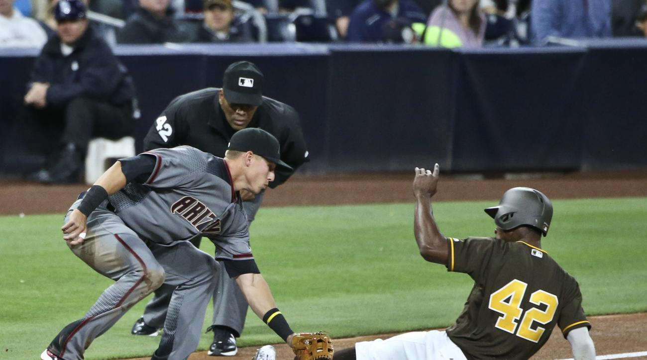 San Diego Padres' Melvin Upton Jr. s;ides under the tag of Arizona Diamondbacks third baseman Jake Lamb while stealing a base during the second inning of a baseball game Friday, April 15, 2016, in San Diego. The umpire is Laz Diaz. (AP Photo/Lenny Ignelzi