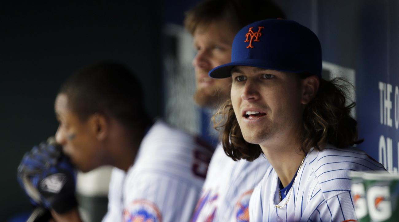 FILE - In this April 8, 2016, file photo, New York Mets pitcher Jacob deGrom (48) watches from the dugout during the fourth inning of a baseball game against the Philadelphia Phillies in New York. The Mets placed deGrom on the family medical emergency lis