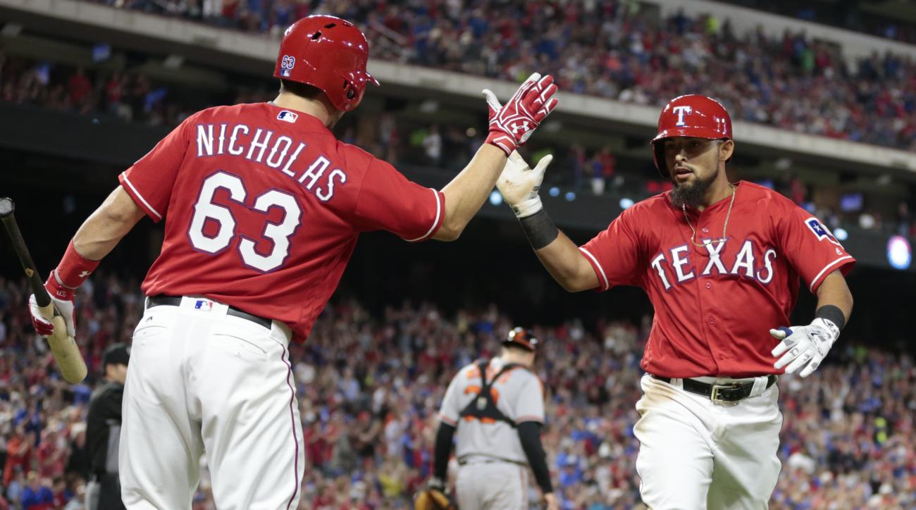Texas Rangers' Rougned Odor, right, celebrates his run with Brett Nicholas (63) on a single by Elvis Andrus against the Baltimore Orioles during the seventh inning of a baseball game, Saturday, April 16, 2016, in Arlington, Texas. (AP Photo/Jim Cowsert)