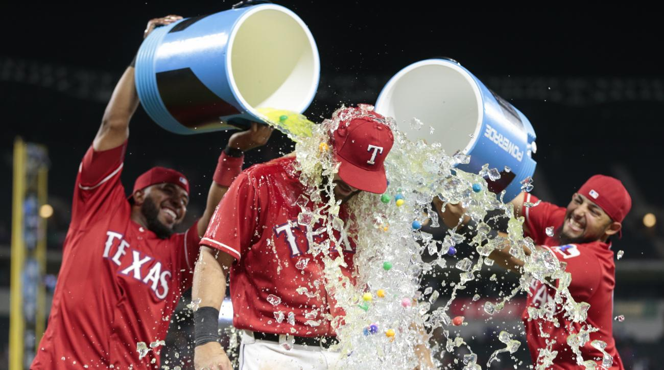 Texas Rangers' Mitch Moreland, center, is doused by teammates Elvis Andrus, left, and Rougned Odor following their teams 8-4 win over the Baltimore Orioles during the seventh inning of a baseball game, Saturday, April 16, 2016, in Arlington, Texas. (AP Ph