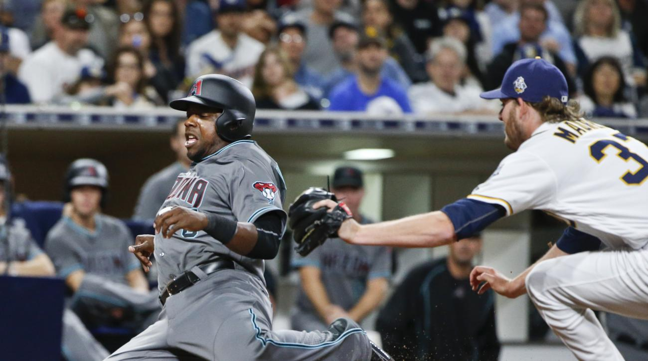 Arizona Diamondbacks' Rickie Weeks beats the tag of San Diego Padres relief pitcher Brandon Maurer as he scores the tying run on a wild pitch during the eighth inning of a baseball game Saturday, April 16, 2016, in San Diego.  (AP Photo/Lenny Ignelzi)