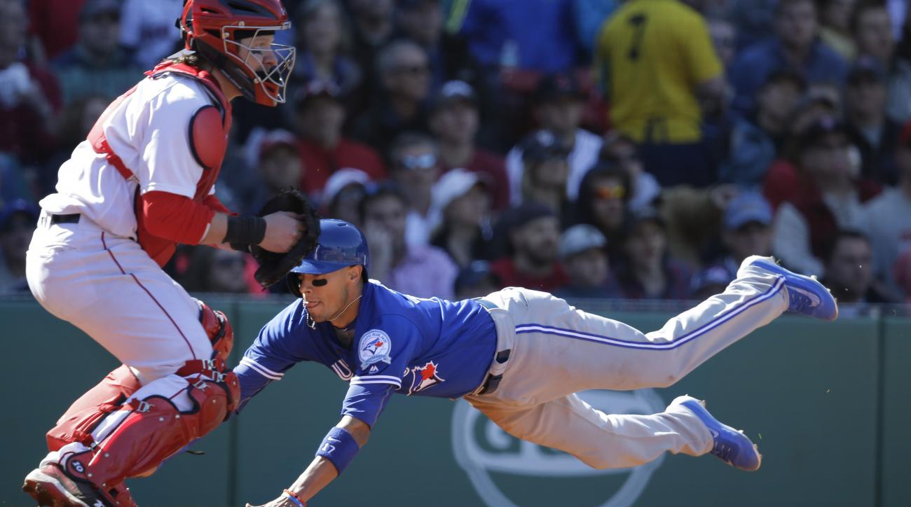 Toronto Blue Jays' Ryan Goins, right, scores as Boston Red Sox catcher Ryan Hanigan, left, waits for the ball in the seventh inning of a baseball game at Fenway Park, Sunday, April 17, 2016, in Boston. (AP Photo/Steven Senne)