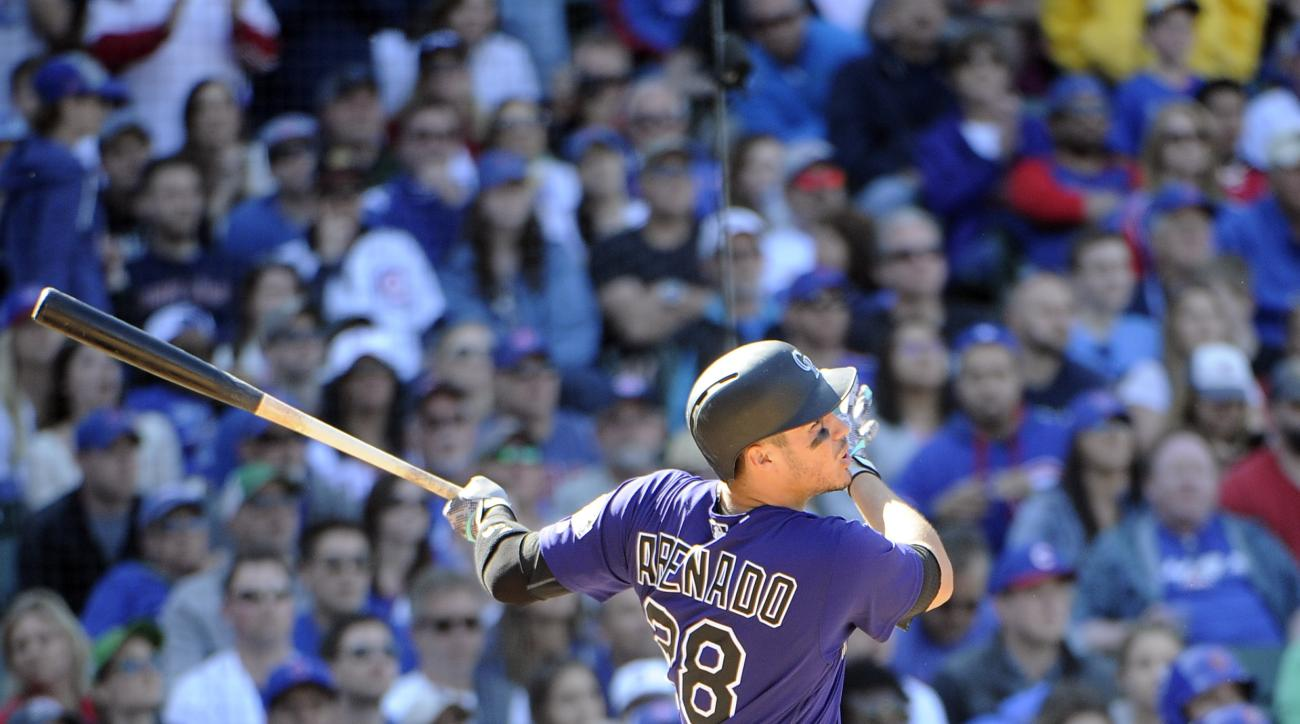 Colorado Rockies' Nolan Arenado (28) hits a solo home run against the Chicago Cubs during the ninth inning of a baseball game, Sunday, April 17, 2016, in Chicago. (AP Photo/David Banks)