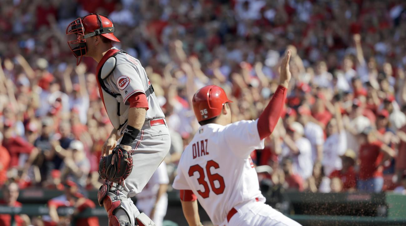 St. Louis Cardinals' Aledmys Diaz, right, scores past Cincinnati Reds catcher Devin Mesoraco during the eighth inning of a baseball game, Sunday, April 17, 2016, in St. Louis. The Cardinals won 4-3. (AP Photo/Jeff Roberson)