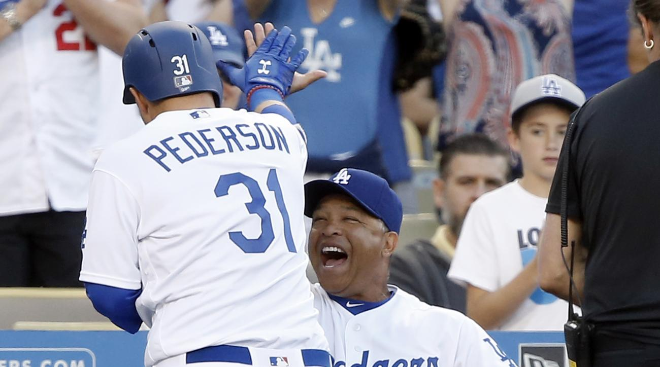 Los Angeles Dodgers' Joc Pederson, left, gets congratulations from manager Dave Roberts (30) after hitting a two-run home run against the San Francisco Giants during the fifth inning of a baseball game in Los Angeles, Sunday, April 17, 2016. (AP Photo/Ale