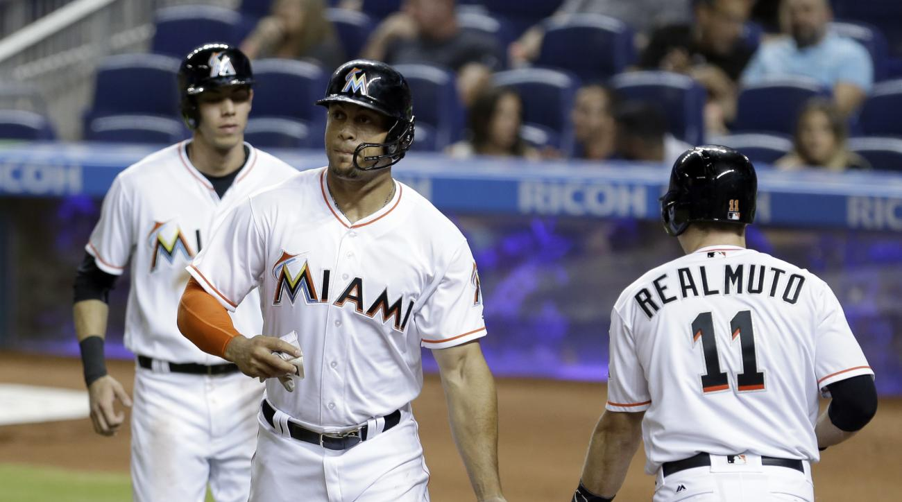 Miami Marlins' Giancarlo Stanton, center, is congratulated by teammate J.T. Realmuto (11) after Stanton and Christian Yelich, left, scored on a single by Marcell Ozuna (13) against the Washington Nationals during the first inning of a baseball game, Monda