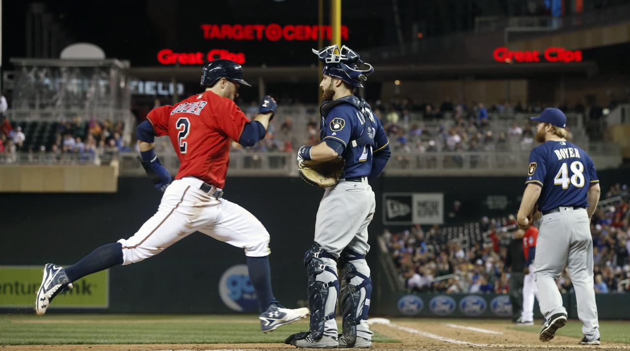 Minnesota Twins' Brian Dozier, left, scores on a double by Joe Mauer off Milwaukee Brewers relief pitcher Blaine Boyer, right, in the sixth inning of a baseball game Monday, April 18, 2016, in Minneapolis. Watching Mauer take second base is catcher Jonath
