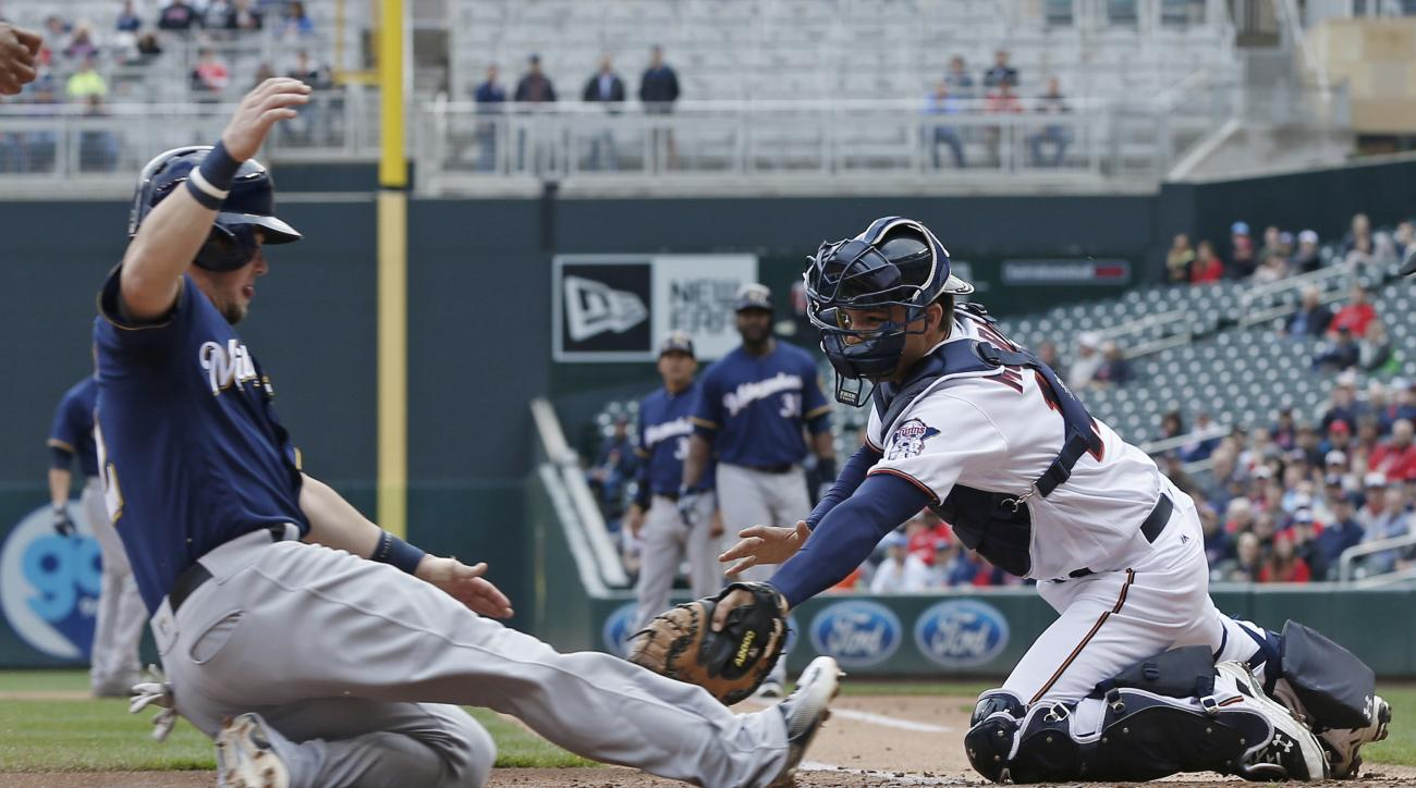 Milwaukee Brewers' Scooter Gennett, left, beats the tag by Minnesota Twins catcher John Ryan Murphy to score from third on a sacrifice fly by Chris Carter in the first inning of a baseball game Tuesday, April 19, 2016, in Minneapolis. (AP Photo/Jim Mone)