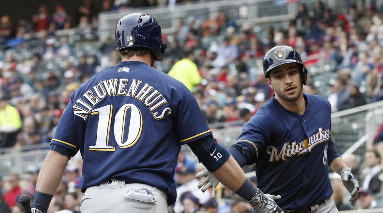 Milwaukee Brewers' Ryan Braun, right, is congratulated by Kirk Nieuwenhuis after scoring on a sacrifice fly by Chris Carter off Minnesota Twins pitcher Ervin Santana, right, in the fifth inning of a baseball game Tuesday, April 19, 2016, in Minneapolis. (