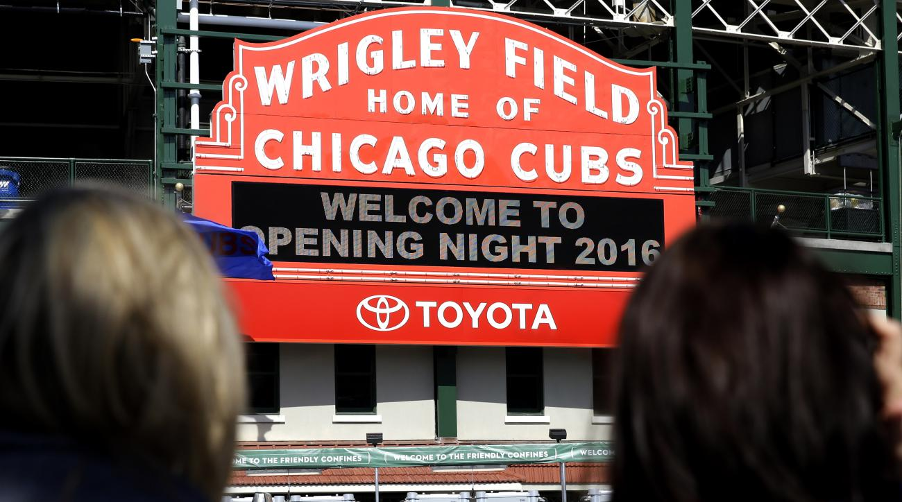 Fans look at the Wrigley Field sign on the street before the start of an opening day baseball game between the Cincinnati Reds and the Chicago Cubs on Monday, April 11, 2016, in Chicago. (AP Photo/Nam Y. Huh)