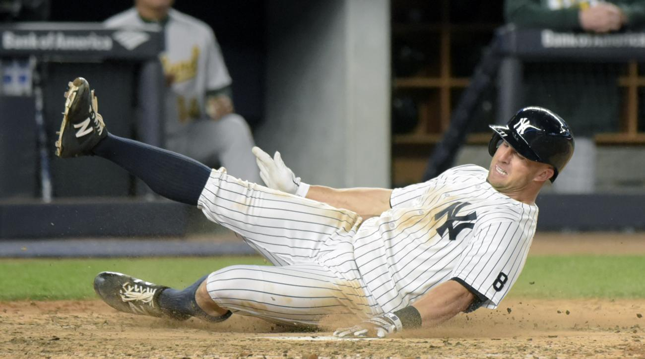 New York Yankees' Brett Gardner scores on a sacrifice fly by Carlos Beltran during the fifth inning of a baseball game against the Oakland Athletics on Tuesday, April 19, 2016, at Yankee Stadium in New York. (AP Photo/Bill Kostroun)
