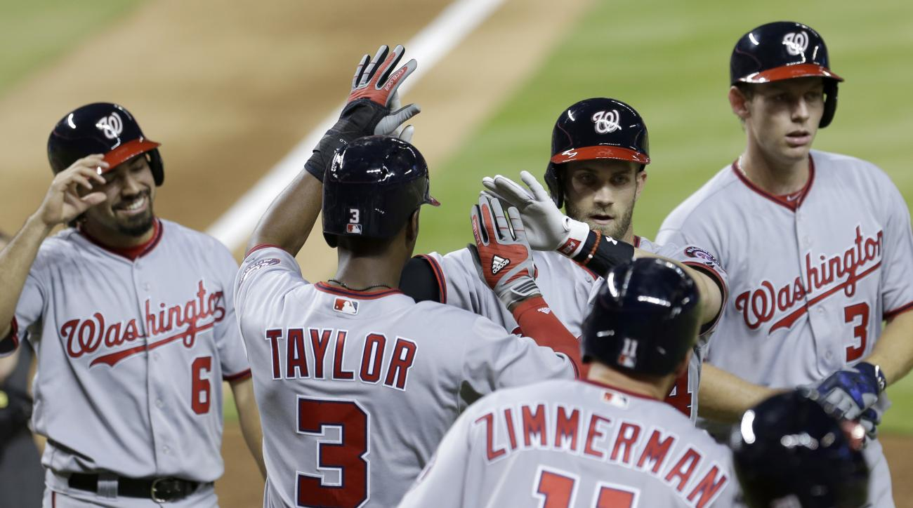 Washington Nationals, Bryce Harper, second from right, is congratulated by teammates Anthony Rendon (6), Michael Taylor (3) and Ryan Zimmerman (11) after Harper's home run with the bases loaded against the Miami Marlins during the seventh inning of a base