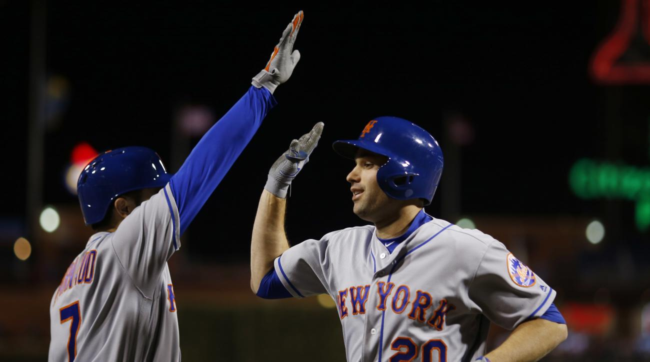 New York Mets' Neil Walker, right, and Travis d'Arnaud celebrate after Walker's home run off Philadelphia Phillies pitcher Brett Oberholtzer during the seventh inning of a baseball game, Tuesday, April 19, 2016, in Philadelphia. New York won 11-1. (AP Pho