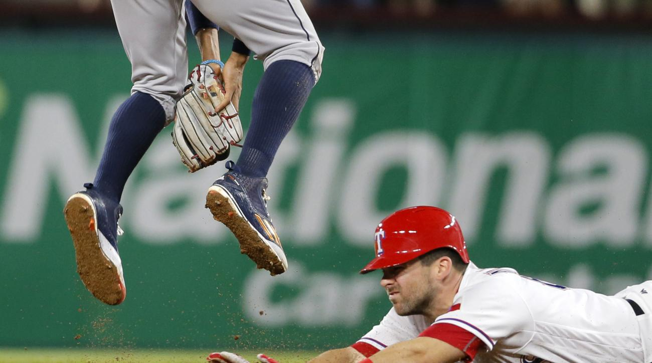 Texas Rangers' Brett Nicholas slides into second for a double as Houston Astros shortstop Carlos Correa leaps to catch the throw from the outfield in the sixth inning of a baseball game, Tuesday, April 19, 2016, in Arlington, Texas. (AP Photo/Tony Gutierr
